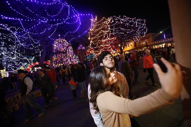 Mikaila Maese, cq, of Albuquerque, and her boyfriend Jesus Velerio, of Santa Fe, take a selfie moments after the lights went on at the Holiday Lighting on the Plaza on Friday, November 24, 2017. Luis Sánchez Saturno/The New Mexican