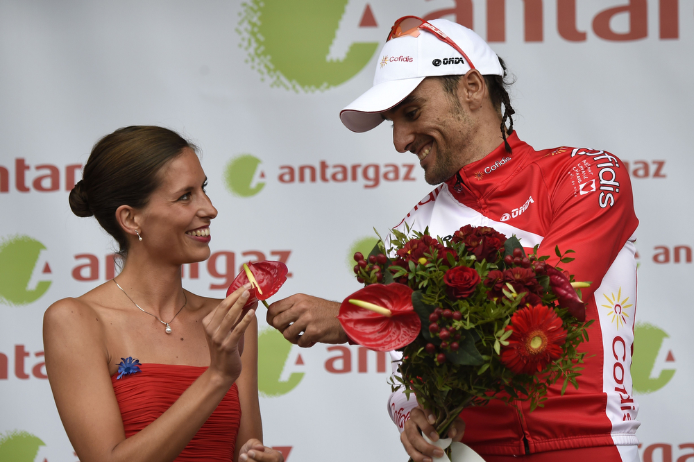 . Spain\'s Luis Angel Mate Mardones offers a flower to a hostess as he celebrates his combativity prize on the podium at the end of the 194 km sixth stage of the 101st edition of the Tour de France cycling race on July 10, 2014 between Arras and Reims, northern France.  (ERIC FEFERBERG/AFP/Getty Images)