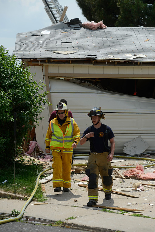 . Fire fighters walk through debris in front of a garage after the house explosion.  (Photo By Andy Cross/The Denver Post)
