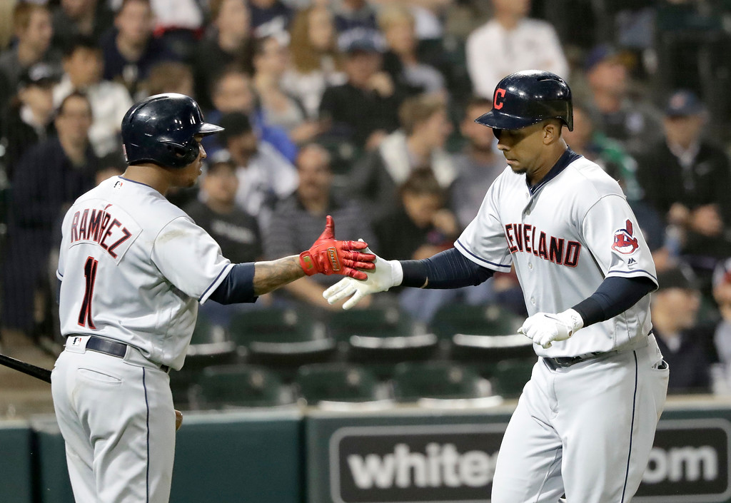 . Cleveland Indians\' Jose Ramirez, left, greets Michael Brantley at home after Brantley\'s home run off Chicago White Sox starting pitcher Lucas Giolito during the fifth inning of a baseball game Monday, June 11, 2018, in Chicago. (AP Photo/Charles Rex Arbogast)