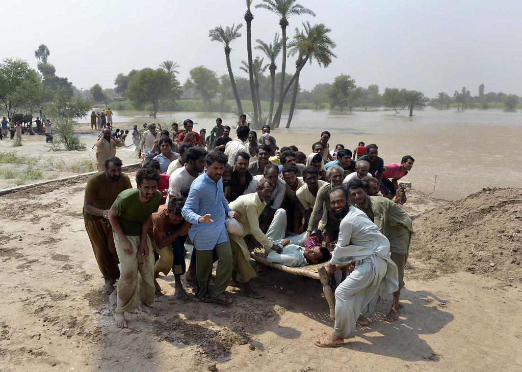 . Residents, affected by flooding, wait to board an army helicopter with injured people in the Peer Kot area of Jhang, in central Punjab province on September 11, 2014.  Pakistani troops on September 11 rushed to protect two major cities from raging floodwaters, using explosives to divert swollen rivers in a crisis which has hit more than a million people and inundated swathes of farmland. The floods and landslides from days of heavy monsoon rains have now claimed more than 450 lives in Pakistan and India, with hospitals struggling to cope with the disaster.   AFP PHOTO/ Arif  Ali/AFP/Getty Images