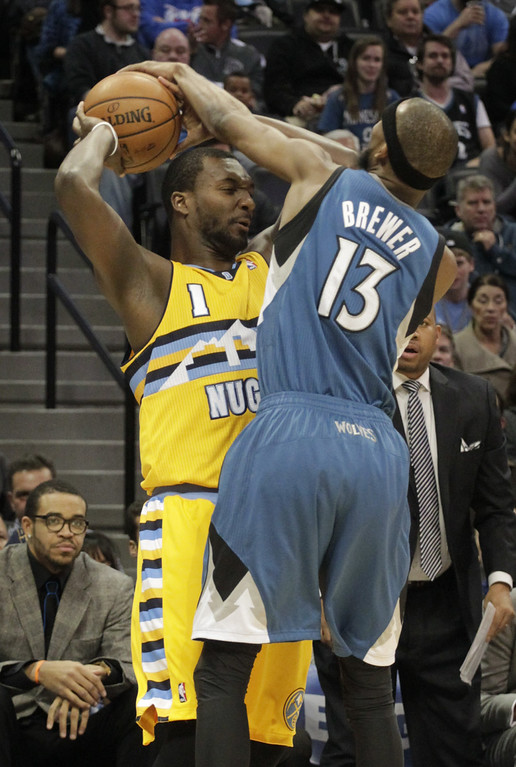 . Minnesota Timberwolves forward Corey Brewer (13) reaches for the ball against Denver Nuggets forward Jordan Hamilton (1) during the first quarter of an NBA basketball game in Denver, Friday, Nov. 15, 2013. (AP Photo/Joe Mahoney)