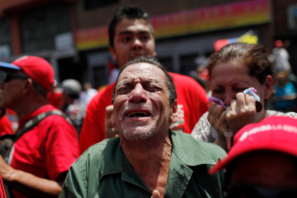 . A man screams as the coffin of Venezuela\'s late President Hugo Chavez passes in the street as it is paraded from the hospital where he died on Tuesday to a military academy where it will remain until his funeral in Caracas, Venezuela, Wednesday, March 6, 2013. (AP Photo/Rodrigo Abd)