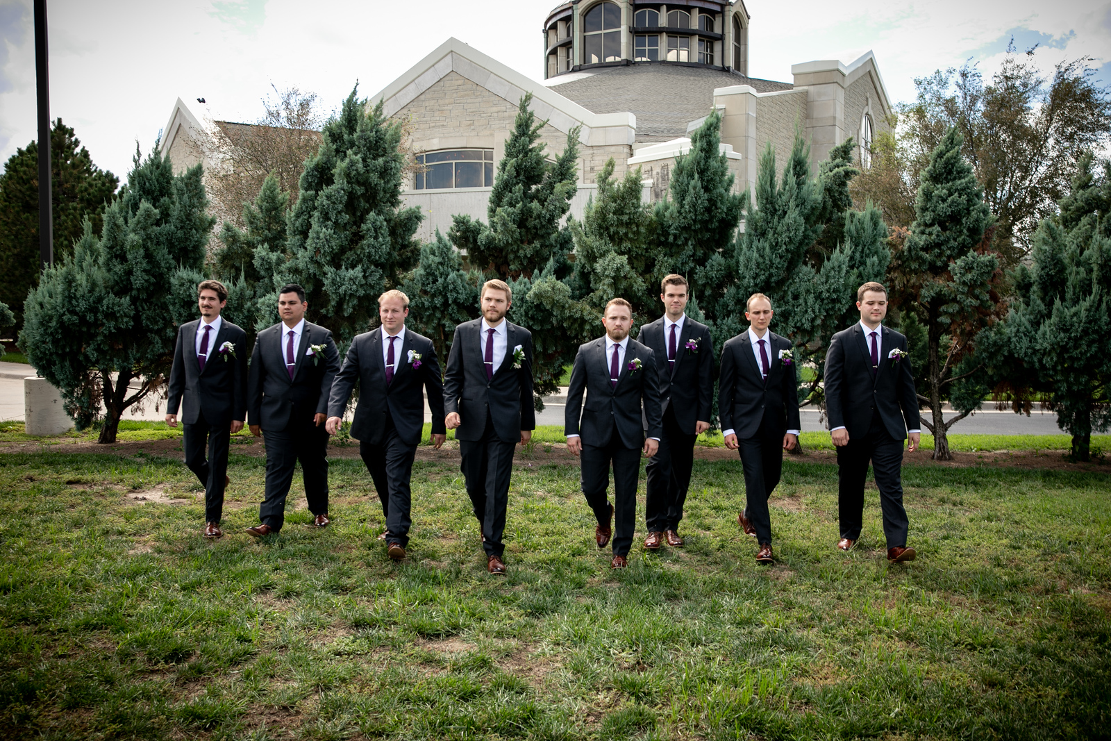 seven groomsmen and a groom walking through a field in front of a church with a serious look