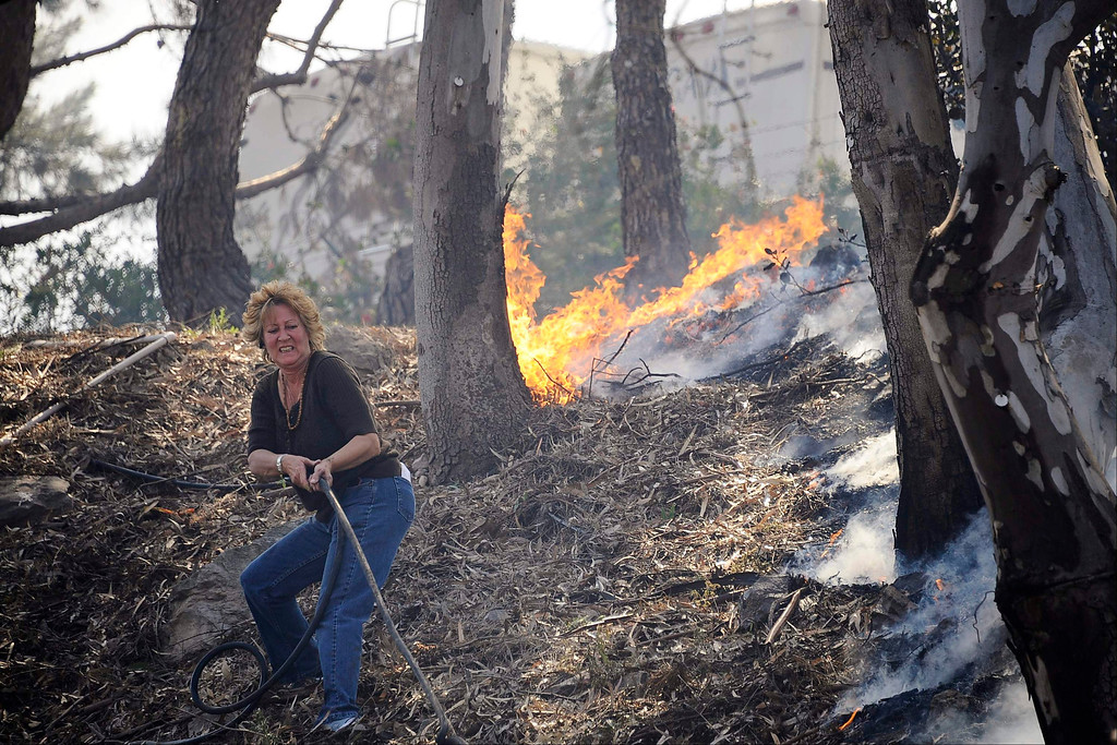 . A resident pulls a hose line to attempt to stop flames from spreading down the hillside as The Springs Fire pushes towards the coast near Camarillo, California May 2, 2013.  REUTERS/Gene Blevins