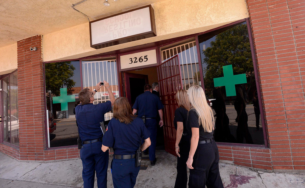 . City Fire and Code Enforcement officers enter a marijuana dispensary during a raid along the 3200 block of North E Street in San Bernardino May 9, 2013. GABRIEL LUIS ACOSTA/STAFF PHOTOGRAPHER.