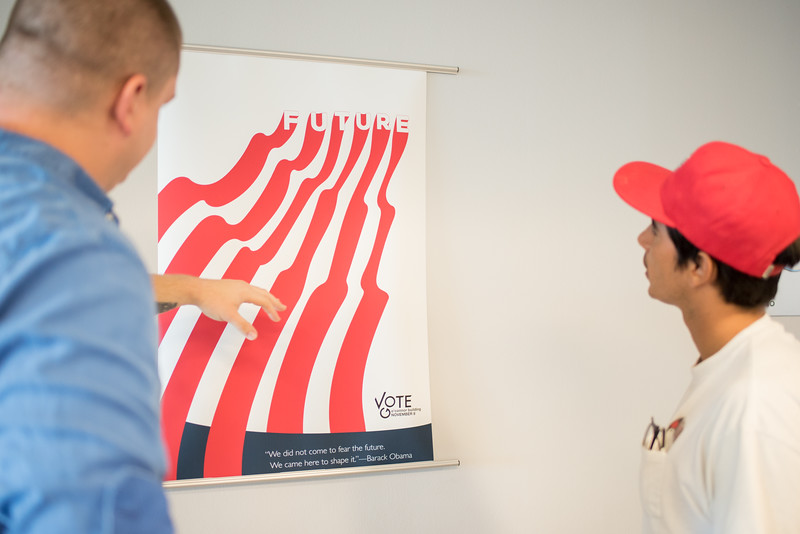 Austin Wilkins and Tony Pena review posters submitted for a graphic design project to encourage students to vote.