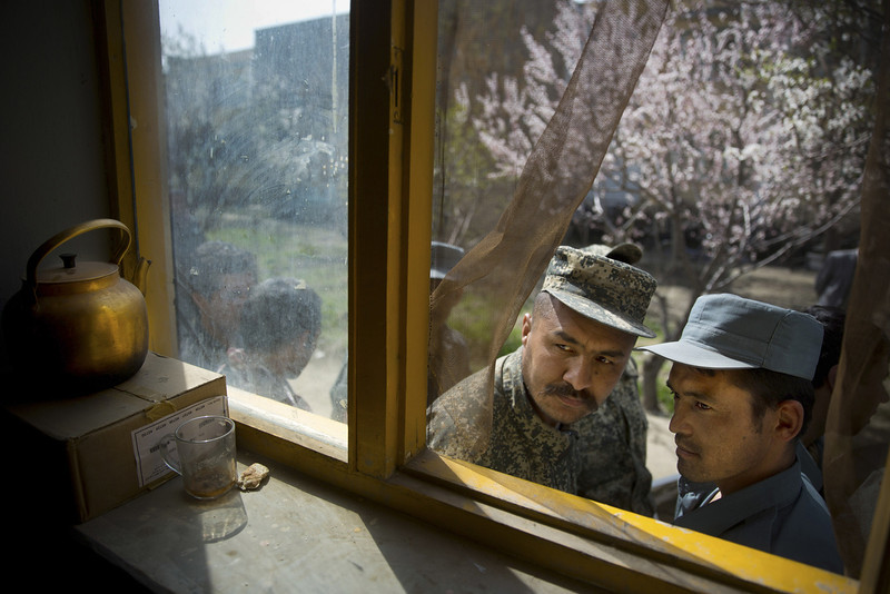. An Afghan soldier, left, and a police man peek through a window as they queue with others to get their registration card on the last day of voter registration for the upcoming presidential elections outside a school in Kabul, Afghanistan, Tuesday, April 1, 2014. Elections will take place on April 5, 2014. (AP Photo/Anja Niedringhaus)