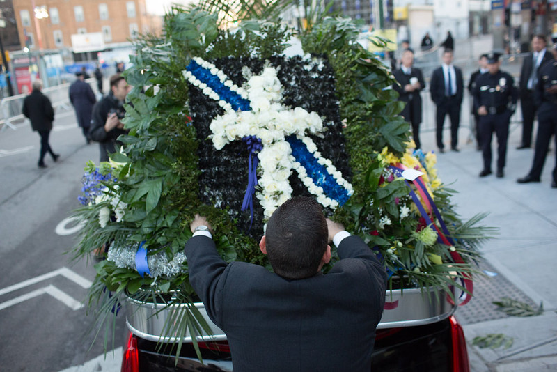 . Church staff place flowers on top of a vehicle before the funeral of slain New York City Police Officer Rafael Ramos, one of two officers murdered while sitting in their patrol car in an ambush in Brooklyn last Saturday afternoon on December 27, 2014 in New York City. Thousands of fellow officers, family, friends and Vice President Joseph Biden are expected at the church in the Glendale neighborhood of Queens for the funeral. (Photo by Kevin Hagen/Getty Images)