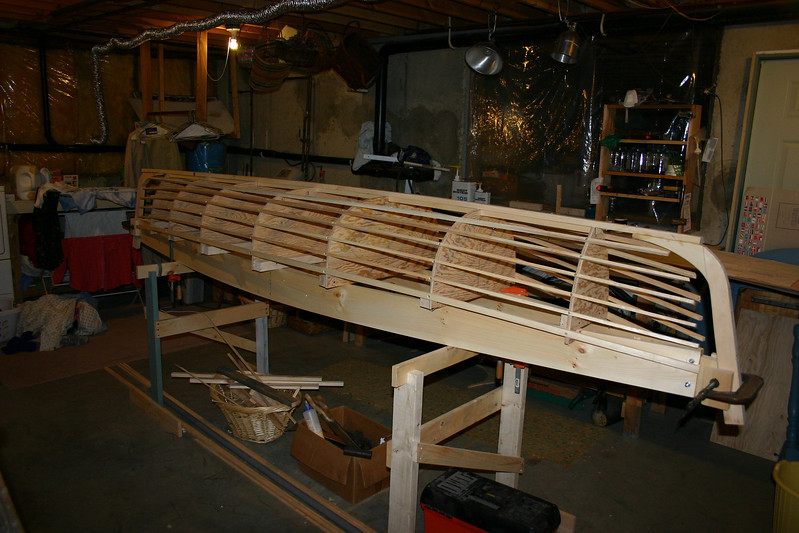 """I purchased a set of plans for a solo canoe from Thomas J. Hill, a boat designer in Burlington. The boat is one of several featured in his book """"Ultralight Boatbuilding."""" The first step was to construct the form, over which the canoe would be built. The form determines the exact shape of the canoe and was constructed of plywood, spruce boards, and spruce strips. In this picture the first two pieces of the actual canoe, the keelson and the stem, have been attached to the form. I built the canoe in my basement."""