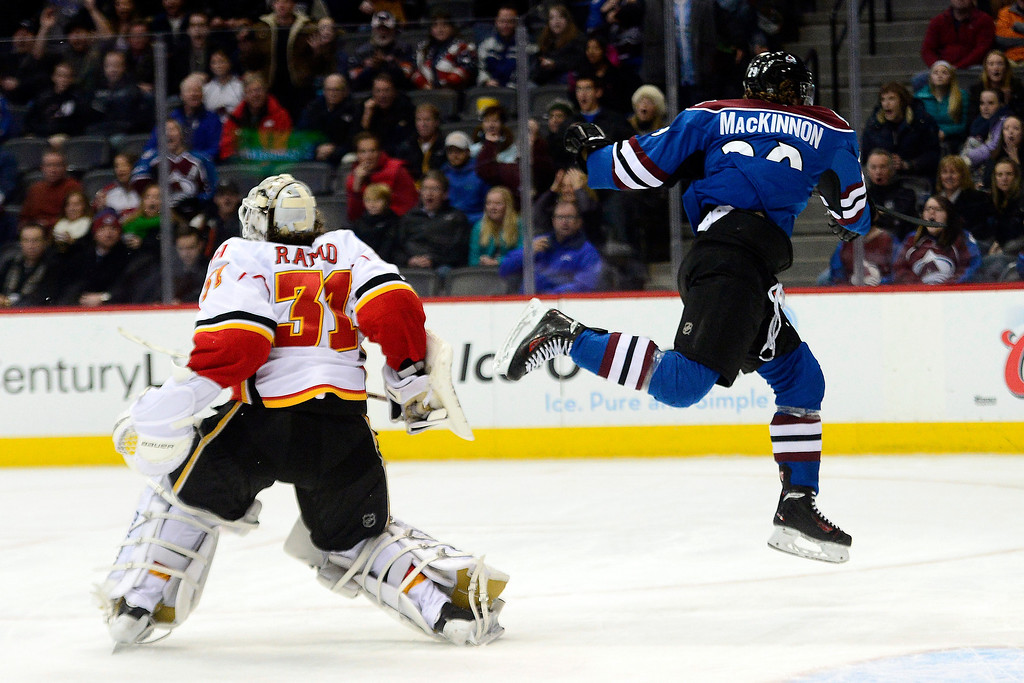 . Nathan MacKinnon (29) of the Colorado Avalanche makes an athletic play after breaking through the defense of Ladislav Smid (3) of the Calgary Flames and T.J. Brodie (7) en route to narrowly missing a hat trick shot on goal against Karri Ramo (31) of the Calgary Flames during the third period of the Flames\' 4-3 win.  (Photo by AAron Ontiveroz/The Denver Post)