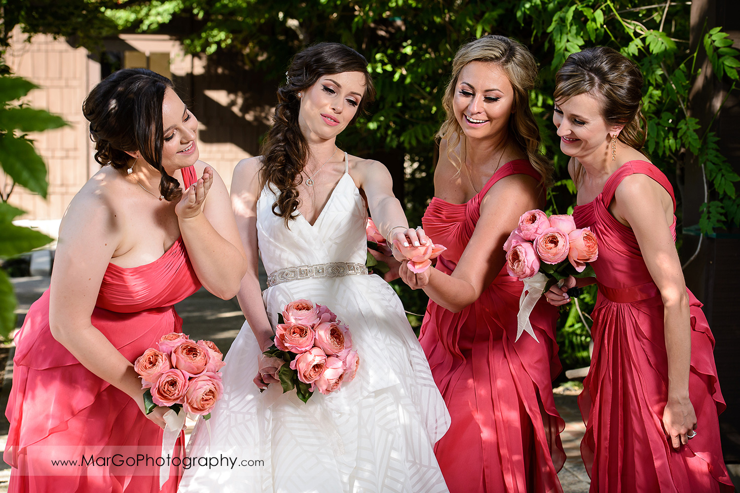 bridesmaids in pink dresses looking at bride's ring at Saratoga Foothill Club