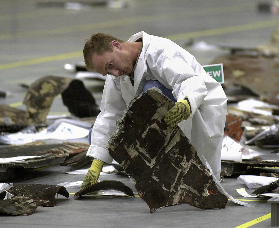 . A space shuttle Columbia reconstruction project team member inspects a piece of wreckage from the orbiter in a hangar at the Kennedy Space Center in Cape Canaveral, Fla. Wednesday April 2, 2003.  (AP Photo/Peter Cosgrove)
