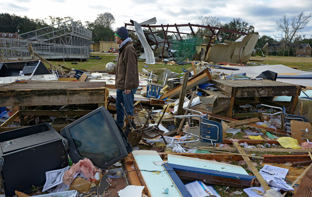 Description of . Murphy High School teacher Leland Howard tries to salvage items where his algebra classroom once stood in a temporary building at Murphy High School as residents clean up and assess the damage from a Christmas Day tornado Wednesday, Dec. 26, 2012  in Mobile, Ala. With only a handful of injuries and no deaths reported statewide from the storms, the head of the state's emergency response said it was difficult to fathom how the toll wasn't worse. (AP Photo/G.M. Andrews)