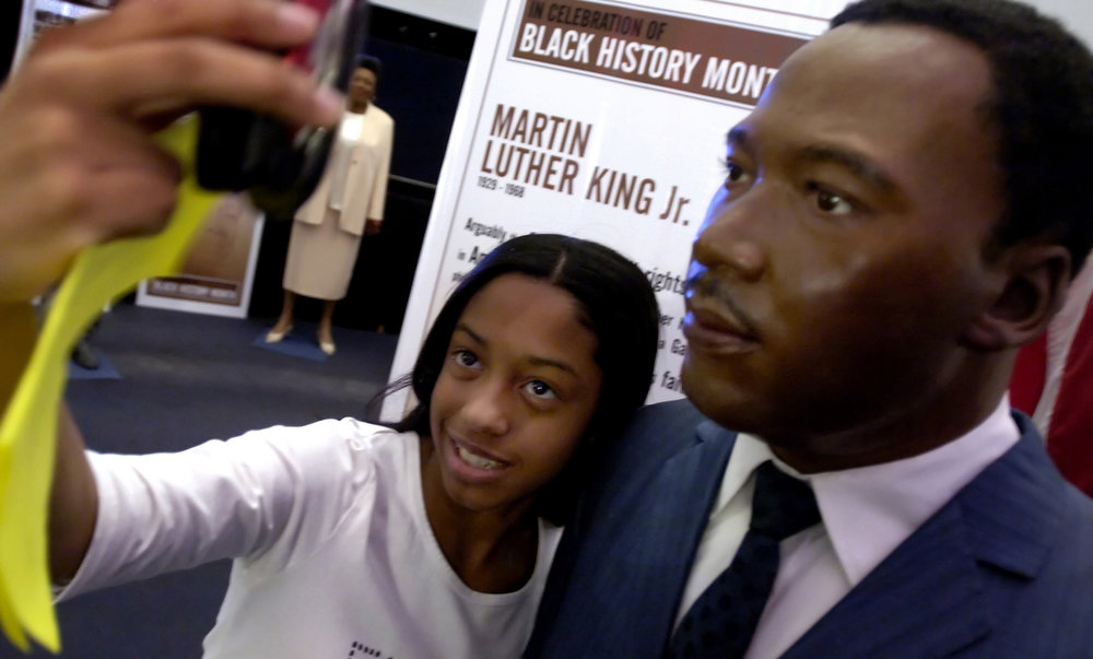 Description of . Alison Hemmings, 14, of Valley Stream, N.Y., takes her picture with a wax figure of Martin Luther King Jr., as she visits an exhibit celebrating Dr. King and the upcoming Black History Month at Madame Tussaud's Thursday, Jan. 12, 2006 in New York.  Dozens of area middle school students visited the exhibit which includes wax figures of Martin Luther King, Jr., Malcolm X, Nelson Mandela, Rosa Parks and nine other prominent African Americans as well as a