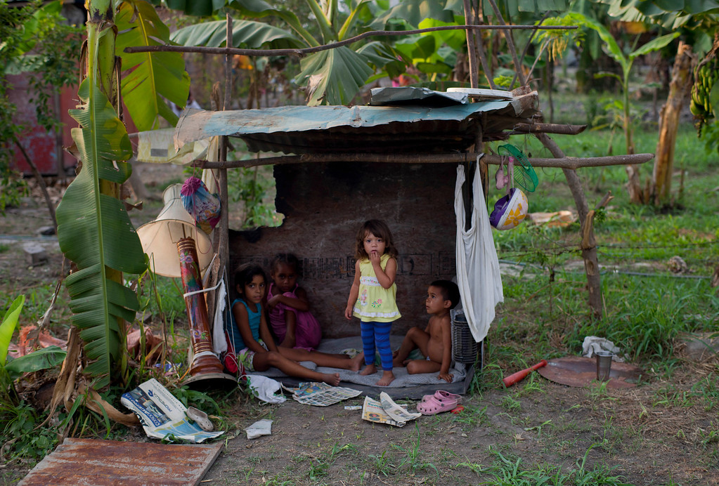 ". In this April 8, 2013 photo, children look out from their playhouse in a squatter settlement near Tacarigua, Venezuela. Outside Venezuela\'s capital, power outages, food shortages and unfinished projects abound; important factors heading into Sunday\'s election to replace Venezuela\'s late President Hugo Chavez, who died last month after a long battle with cancer. An estimated 2 million of the country\'s nearly 30 million people lack permanent homes, and one of Chavez\'s anti-poverty ""missions\"" builds them. But it\'s been slow going. The government says it has built 370,500 homes and apartments over the past two years, and more than 3 million people applied for them. (AP Photo/Ramon Espinosa)"