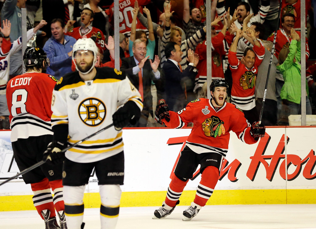 . Chicago Blackhawks center Andrew Shaw, right, celebrates after scoring the winning goal during the third overtime period of Game 1 in their NHL Stanley Cup Final hockey series against the Boston Bruins, Thursday, June 13, 2013, in Chicago. (AP Photo/Nam Y. Huh)