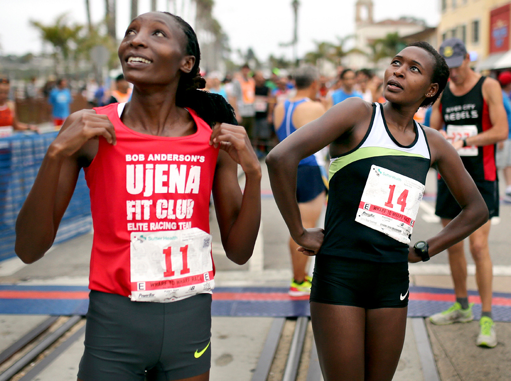 . Elite runners Risper Gesabwa (11) and Sarah Kiptoo (14) meet at the starting line of the 42nd annual Wharf to Wharf in Santa Cruz on Sunday. (Kevin Johnson -- Santa Cruz Sentinel)