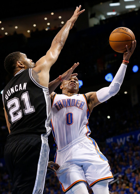 . Oklahoma City Thunder guard Russell Westbrook (0) shoots in front of San Antonio Spurs forward Tim Duncan (21) in the second quarter of Game 3 of an NBA basketball playoff series in the Western Conference finals, Sunday, May 25, 2014, in Oklahoma City. (AP Photo/Sue Ogrocki)