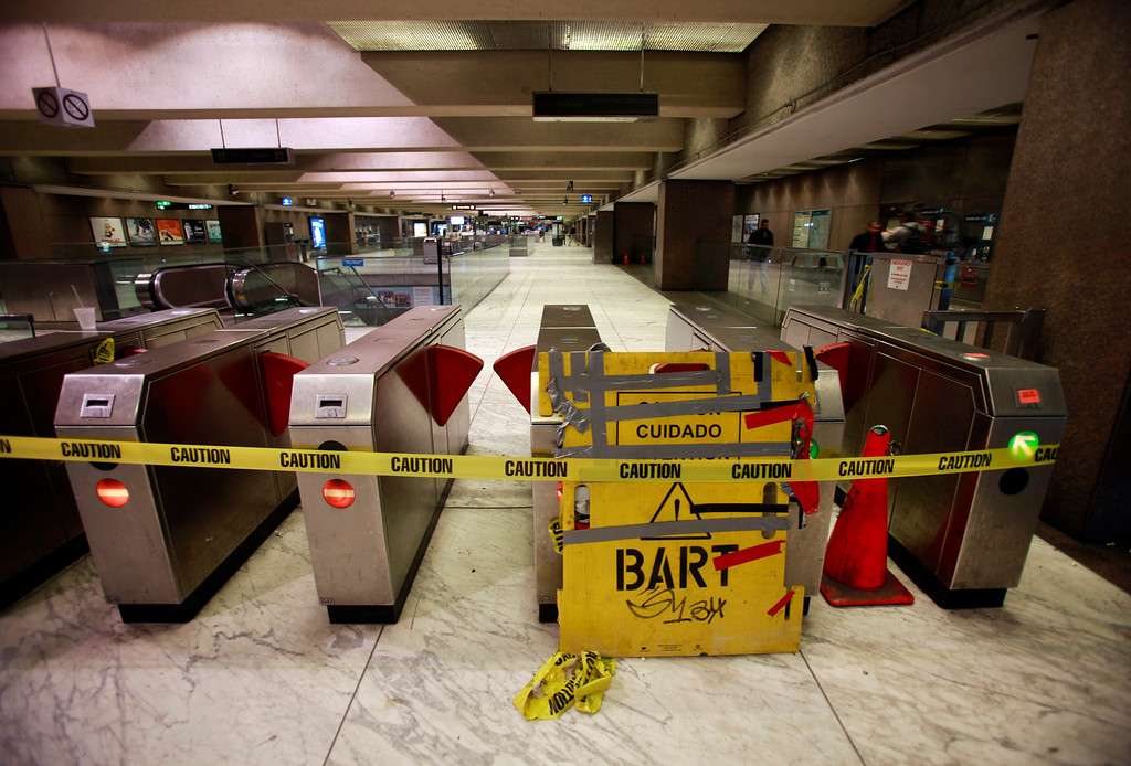 . Caution tape and placards mark the closed fare gates at the Embarcadero BART station in downtown San Francisco Monday morning, July 1, 2013, the first day of the BART strike. (Karl Mondon/Bay Area News Group)