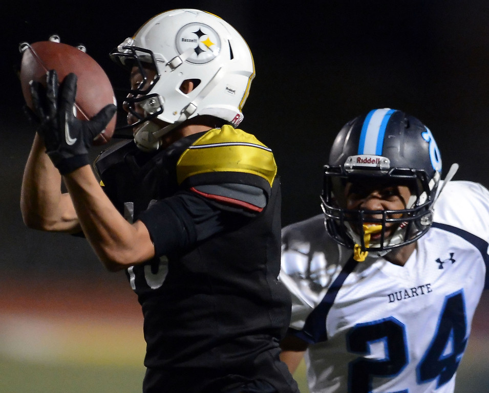 . Bassett\'s Christopher Rios (13) catches a pass in front of Duarte\'s Davante Robinson (24) in the first half of a prep football game at Bassett High School in La Puente, Calif., on Friday, Nov. 1, 2013.    (Keith Birmingham Pasadena Star-News)