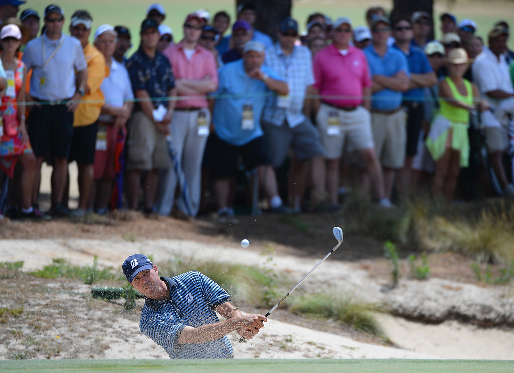 . Matt Kuchar of the United States hits a shot from a bunker on the 16th hole as a gallery of fans look on during the first round of the 114th U.S. Open at Pinehurst Resort & Country Club, Course No. 2 on June 12, 2014 in Pinehurst, North Carolina.  (Photo by Ross Kinnaird/Getty Images)