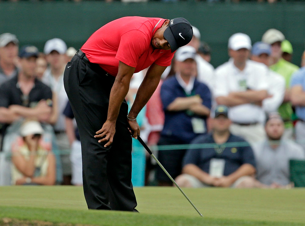 Description of . Tiger Woods reacts after missing a birdie putt on the first hole during the fourth round of the Masters golf tournament Sunday, April 14, 2013, in Augusta, Ga. (AP Photo/Charlie Riedel)