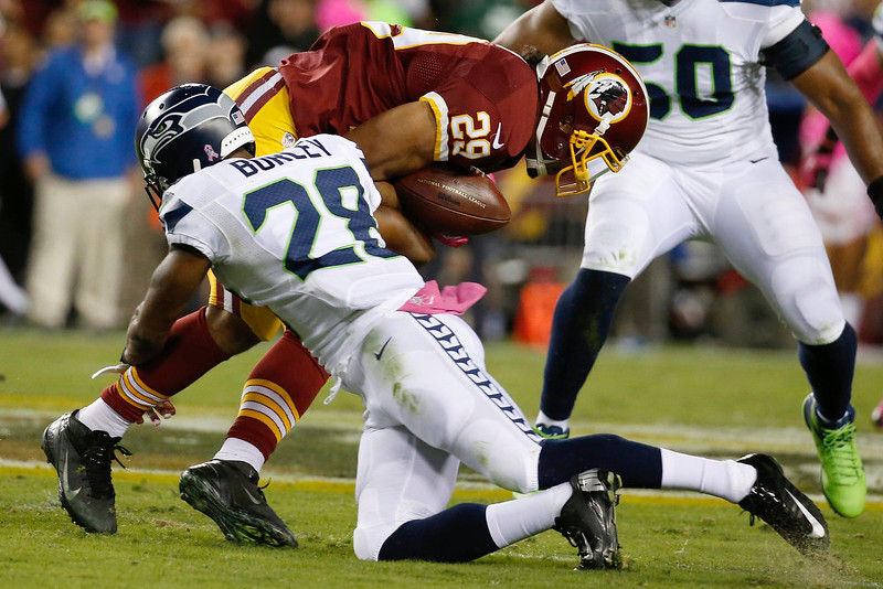 . Washington Redskins running back Roy Helu (29) is stopped by Seattle Seahawks defensive back Marcus Burley (28) during the first half of an NFL football game in Landover, Md., Monday, Oct. 6, 2014. (AP Photo/Alex Brandon)
