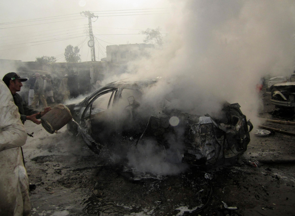 . A policeman tries to extinguish a burning car, after a bomb attack at Fauji Market in Peshawar December 17, 2012. At least 12 people were killed on Monday when the blast struck the market area in Pakistan\'s volatile tribal belt, a security official said. The official said at least 20 people had been wounded in the blast in Fauji Market in the Khyber tribal agency and that the death toll could rise because many were in a critical condition. There was no immediate claim of responsibility. REUTERS/Ameerzada Afridi