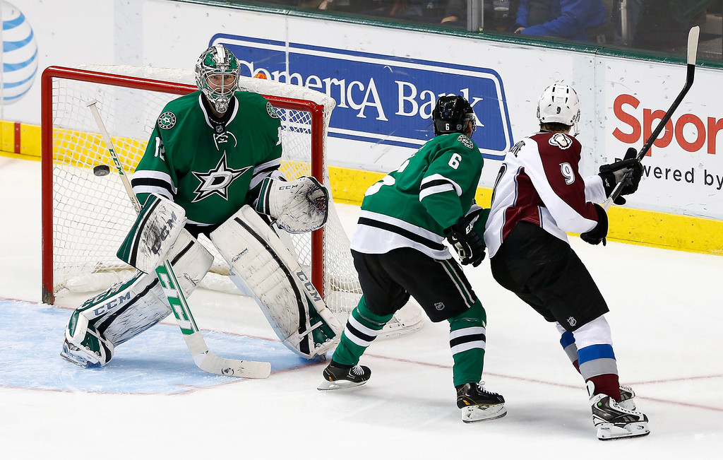 . Kari Lehtonen #32 of the Dallas Stars deflects a shot against Matt Duchene #9 of the Colorado Avalanche in the third period at American Airlines Center on January 27, 2014 in Dallas, Texas.  (Photo by Tom Pennington/Getty Images)