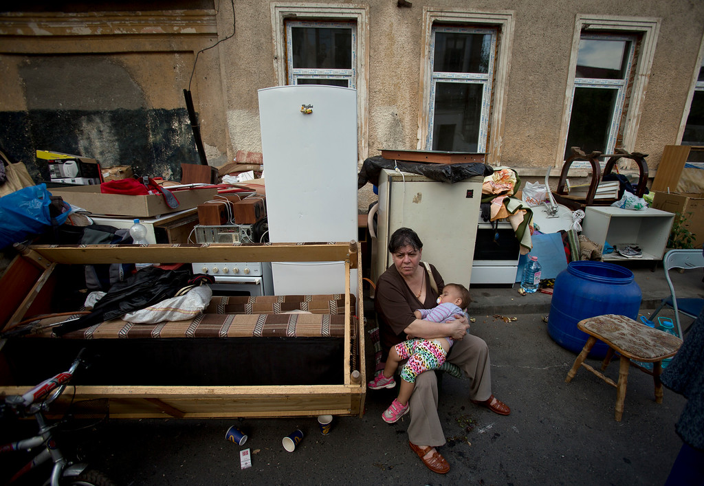 . A Roma child sleeps as a woman sits by belongings moved to the street during the eviction of more than 100 people from the homes they lived in Bucharest, Romania, Monday, Sept. 15, 2014. (AP Photo/Vadim Ghirda)