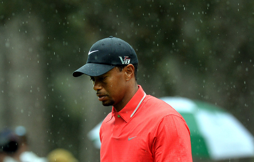 Description of . Tiger Woods of the US walks in the rain during the fourth round of the 77th Masters golf tournament at Augusta National Golf Club on April 14, 2013 in Augusta, Georgia.  JEWEL SAMAD/AFP/Getty Images