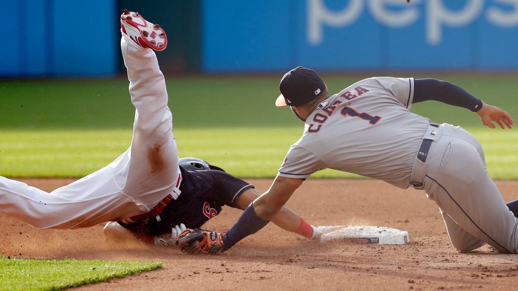 . Houston Astros\' Carlos Correa, right, tags out Cleveland Indians\' Melky Cabrera at second base in the fourth inning of a baseball game, Thursday, May 24, 2018, in Cleveland. (AP Photo/Tony Dejak)