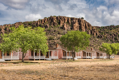 Several brick structures with white wooden porches in west Texas landscape