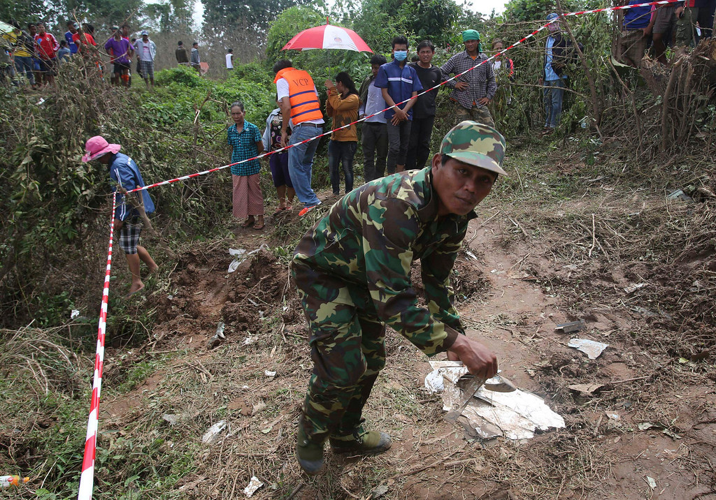 . A Laos soldier works at the scene of the Laos Airlines plane crash in Pakse, Laos Thursday, Oct. 17, 2013.  (AP Photo/Sakchai Lalit)