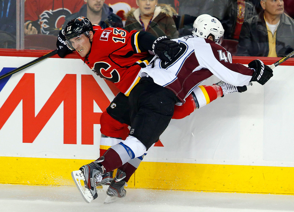 . Calgary Flames\' Mike Cammalleri (L) gets hit against the boards by Colorado Avalanche\' Mark Olver during the second period of their NHL hockey game in Calgary, Alberta, January 31, 2013. REUTERS/Todd Korol