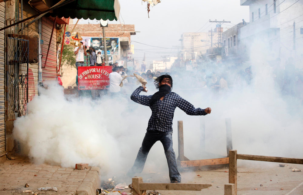 . A Pakistani Christian throws a tear-gas canister to the police during a protest against Saturday\'s burning of their houses and belongings in Badami Bagh, Lahore March 10, 2013. Hundreds of Pakistani Christians took to the streets across the country on Sunday, demanding better protection after a Christian neighborhood was torched in the city of Lahore a day earlier in connection with the country\'s controversial anti-blasphemy law.  REUTERS/Mohsin Raza