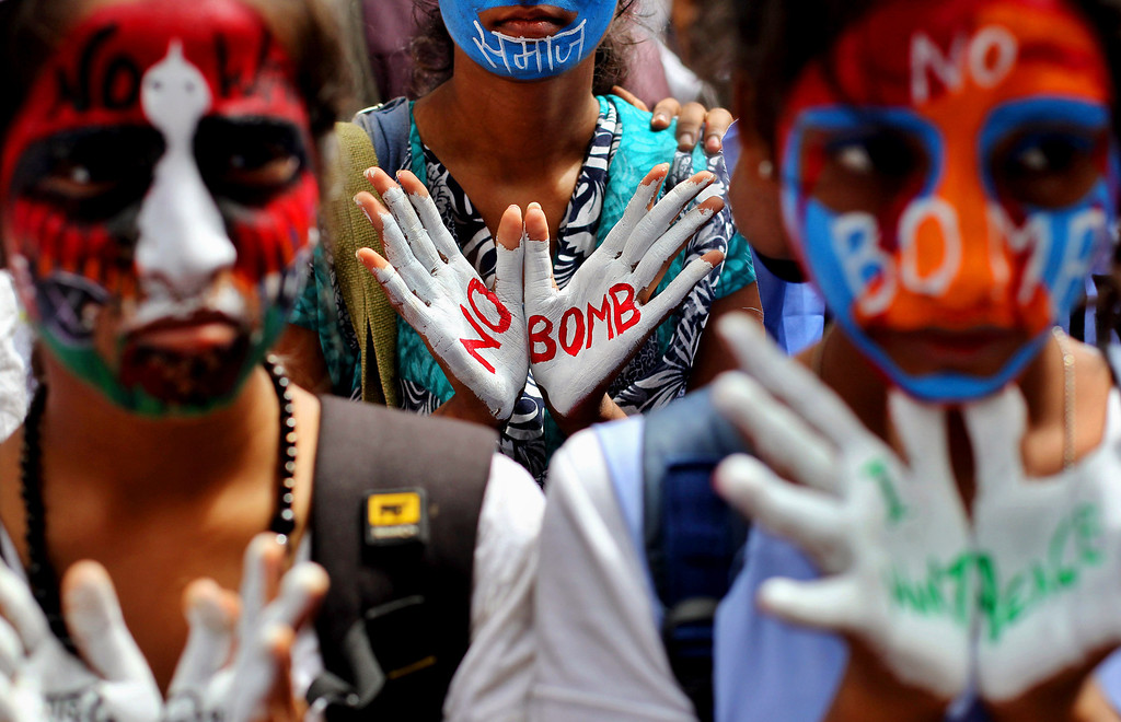 . Indian students with their faces painted in colors, participate in a Hiroshima Day peace rally in Mumbai, India, Tuesday, Aug. 6, 2013.  (AP Photo/Rafiq Maqbool)