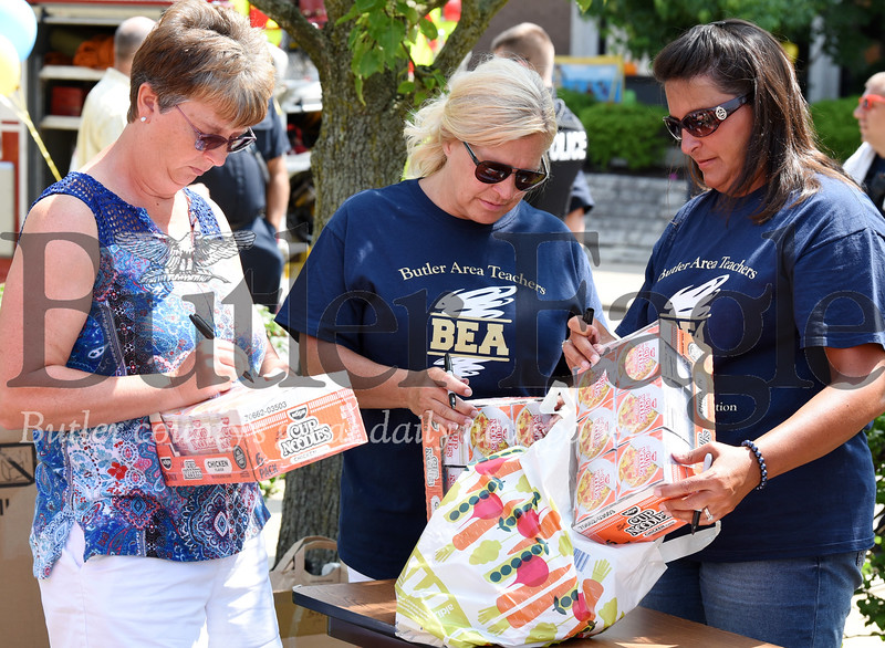 Harold Aughton/Butler Eagle: Butler teachers Ann Mato, Carla Boben and Kim West volunteered Tuesday during the Stuff A Bus event hled at the Emily Brittain School.