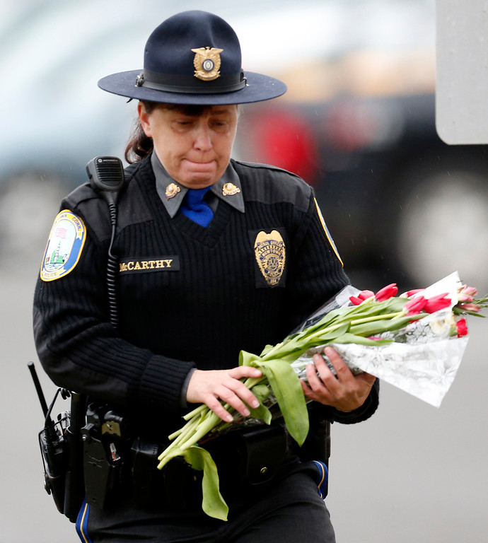 . Newtown Police Officer Maryhelen McCarthy places flowers at a makeshift memorial outside St. Rose of Lima Roman Catholic Church, Sunday, Dec. 16, 2012, in Newtown, Conn. On Friday, a gunman allegedly killed his mother at their home and then opened fire inside the Sandy Hook Elementary School, killing 26 people, including 20 children. (AP Photo/Julio Cortez)
