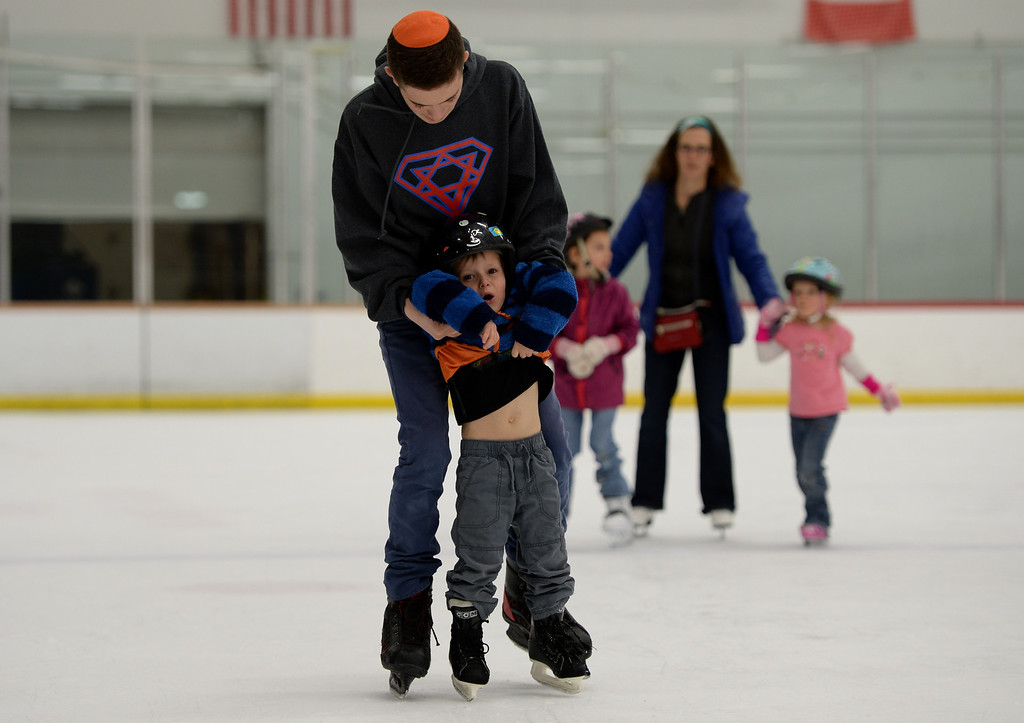 . CENTENNIAL, CO. DECEMBER 25: Yan Kaufman, 13, top, is teaching ice skating to Shia Drexler, 3, at the the South Suburban Sports Center in Centennial, Colorado on December 25, 2013. For the fourteenth year, the Denver Community Kollel Women\'s Division is offering a Jewish Family Extravaganza of family fun and entertainment.  (Photo by Hyoung Chang/The Denver Post)