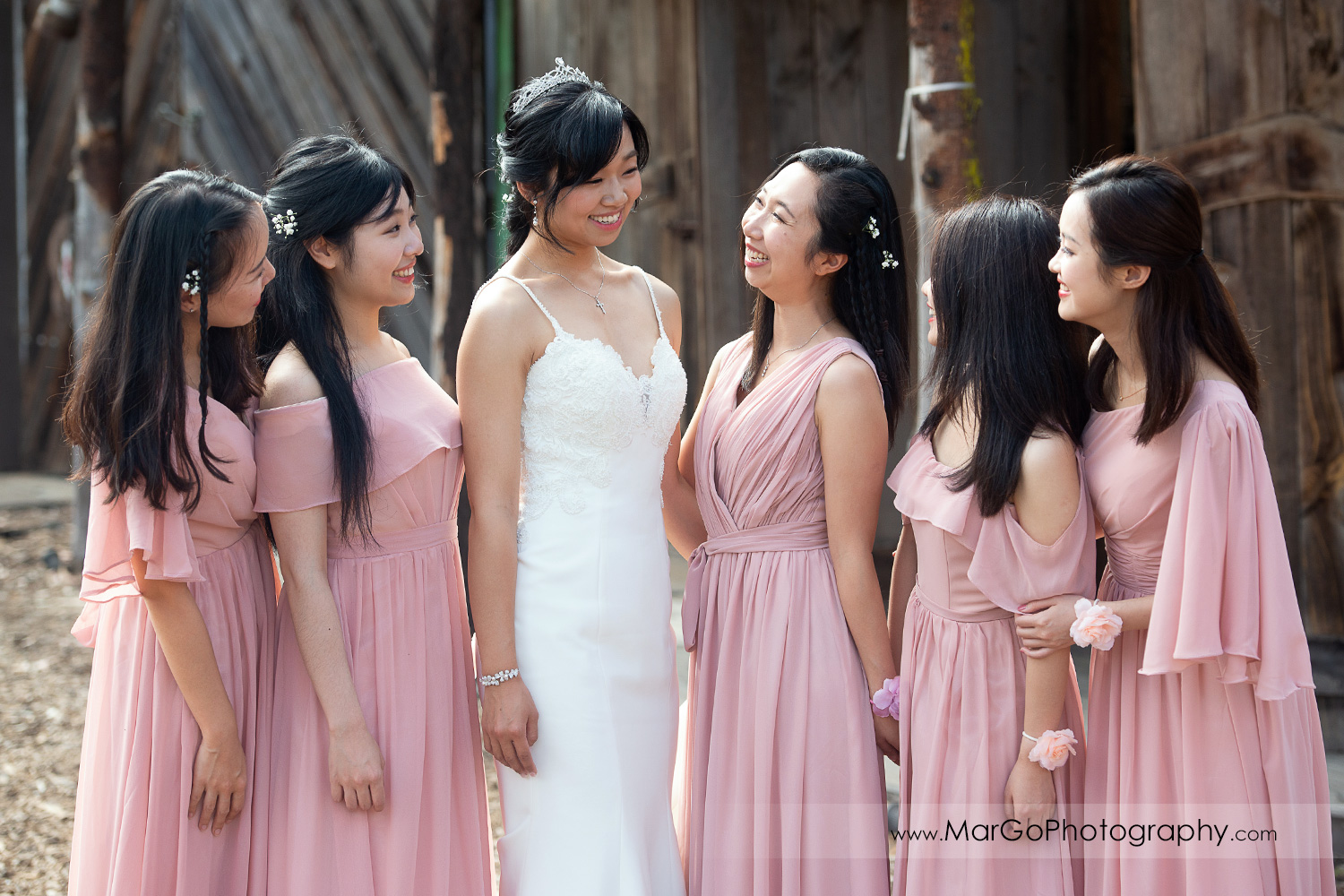 portrait of bride in white dress and bridesmaids in pink dresses looking at each otherat Long Branch Saloon & Farms in Half Moon Bay