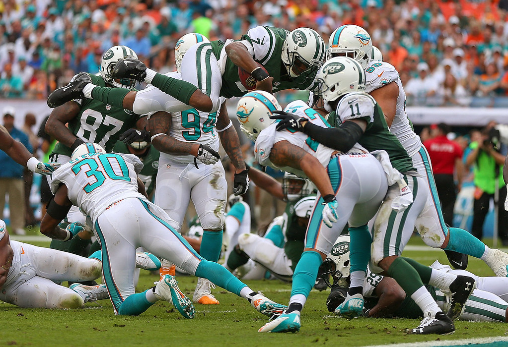 . Geno Smith #7 of the New York Jets dives for a first down during a game against the Miami Dolphins at Sun Life Stadium on December 29, 2013 in Miami Gardens, Florida.  (Photo by Mike Ehrmann/Getty Images)