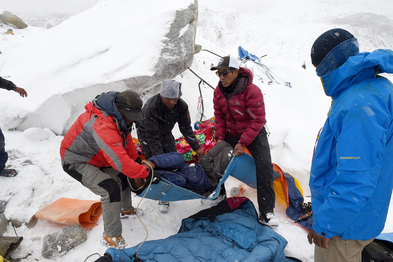 . Rescuers help a porter onto a makeshift stretcher after he was injured by an avalanche caused by an earthquake, before being evacuated to a medical tent in another area of Everest Base Camp.   Rescuers in Nepal are searching frantically for survivors of a huge quake on April 25, that killed nearly 2,000, digging through rubble in the devastated capital Kathmandu and airlifting victims of an avalanche at Everest base camp.  ROBERTO SCHMIDT/AFP/Getty Images