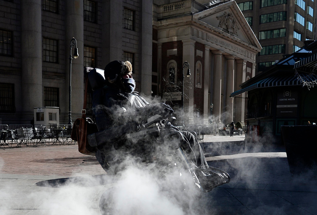 . A woman in wheelchair passes a steam grate in Lower Manhattan Borough of New York, New York, USA, 07 January 2013. Many parts of the United States are experiencing record cold temperatures due to an usual polar vortex of arctic air.  EPA/ANDREW GOMBERT