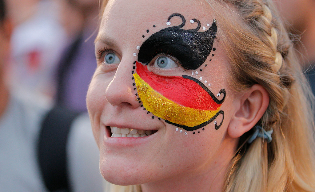 . A Germany soccer fan, with her face painted with her nation\'s colors watches her team\'s World Cup round of 16 match against Algeria on a live telecast inside the FIFA Fan Fest area on Copacabana beach in Rio de Janeiro, Brazil, Monday, June 30, 2014. (AP Photo/Leo Correa)