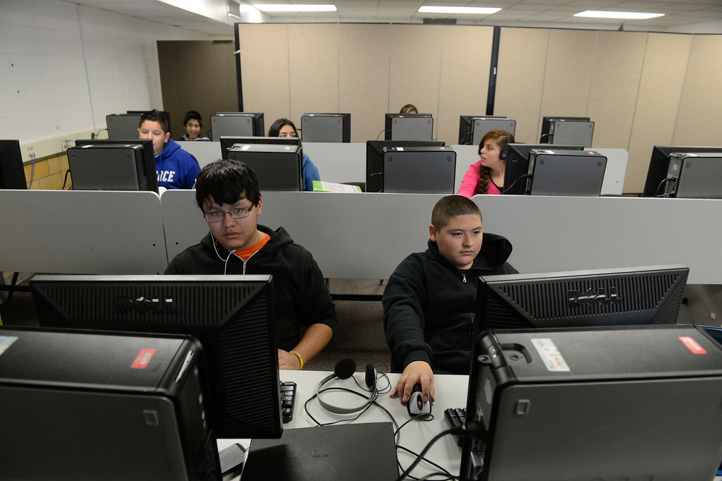 . COMMERCE CITY, CO - NOVEMBER 08:  Kearney Middle School students,   Angel Flores-Mancinas, 14, front left, and classmate, Joel Lucio-Rosales, fron right, work on a math project in a computer lab Friday morning, November 08, 2013. The partition in the back of the room, separates the lab from a teacher lounge/copy room due to the lack of space at the school. The building is in dire need of repairs, but voters voted against a tax measure that would have replaced the school. (Photo By Andy Cross/The Denver Post)