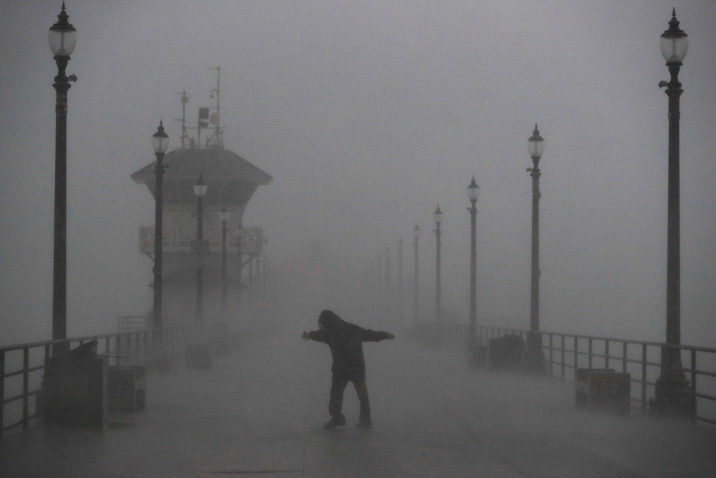 . A man struggles against gusty wind and heavy rain as he walks along a pier Friday, Feb. 17, 2017, in Huntington Beach, Calif. A major Pacific storm has unleashed downpours and fierce gusts on Southern California, triggering flash flood warnings and other problems. (AP Photo/Jae C. Hong)