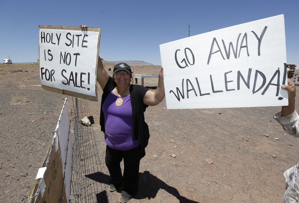 . Renae Yellowhorse, a Navajo from Cameron,  gathers with others American Indians along highway, near Cameron, Ariz., on Sunday, June 23, 2013 to protest Florida aerialist Nik Wallenda\'s tightrope walk over the Little Colorado River Gorge. Wallenda planned the stunt without a safety harness on the Navajo reservation. (AP Photo/Rick Bowmer)