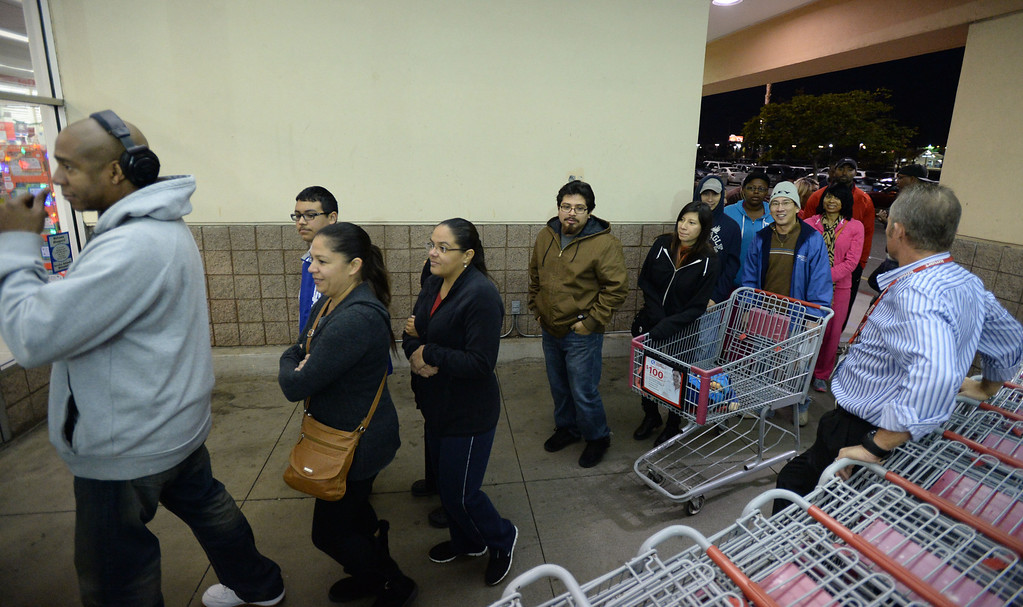 . People gather in the pre-dawn hours to be the first inside Kmart for their 6am opening Thursday, November 28, 2013, in Carson, CA. Store manager Lance Doty, right, greets shoppers as they enter the store. Photo by Steve McCrank/DailyBreeze
